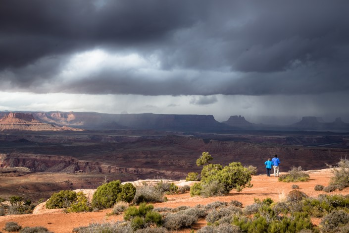 people watching a storm blowing in over canyonlands national park