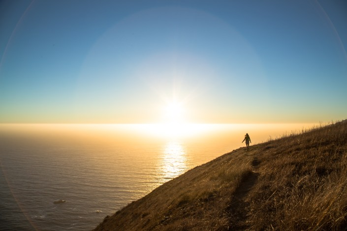 W hiker walks a trail at sunset along the ocean at sunset