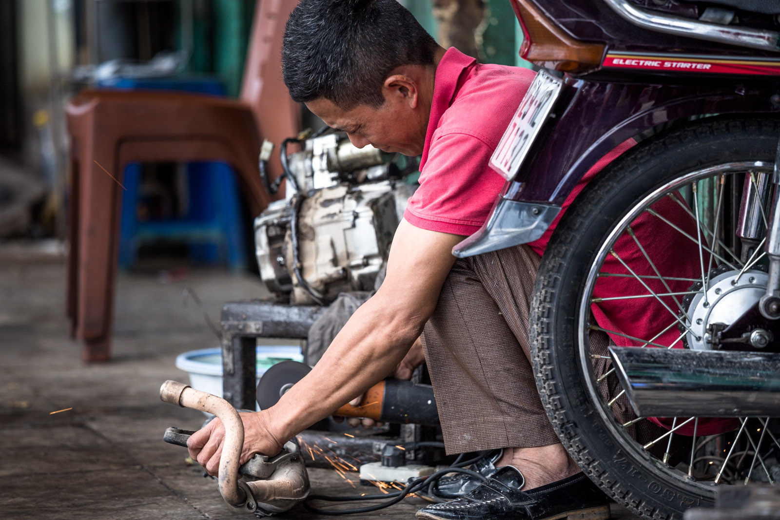man fixing a motorbike part in hanoi