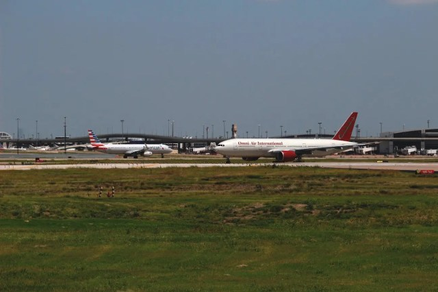 Omni Air International 767 taxiing in the foreground; American A321 taking off in the background.