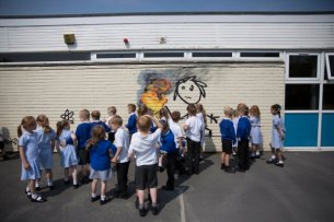 Students at the Bridge Farm Primary School in Hartcliffe, Bristol, gather round anew Banksy mural drawn recently inside the school property. June 6 2016. See SWNS story SWBANKSY: Pupils and teachers returned to their school after half-term to find a genuine BANKSY on the wall of classroom. The famous artist spray painted a stick-wielding child chasing a burning tyre on the side of Bridge Farm Primary School. It is believed the work is a modern take on hoop rolling, a popular game played by children during the Victorian days. The six-foot high artwork also features a flower and a small house with 'Banksy' signed to the bottom left of the brick building.