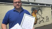Site manager Jason Brady holding a letter left by Banksy at Bridge Farm Primary in Bristol after he painted a mural on the side of one of the classrooms during half-term.