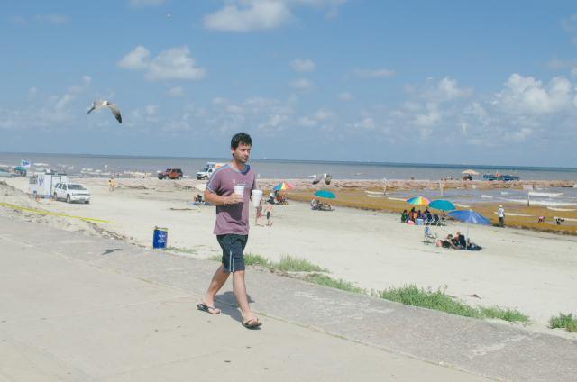 A guy walking along the beach