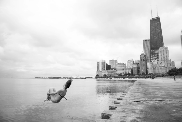 A woman jumping into Lake Michigan at Chicago Beach