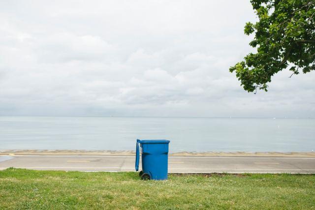 A blue trash can by Lake Michigan