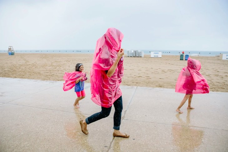 A mom and her daughters running in the rain at Chicago Beach