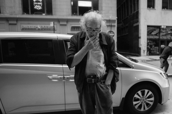 An old man smoking on the street in Chicago