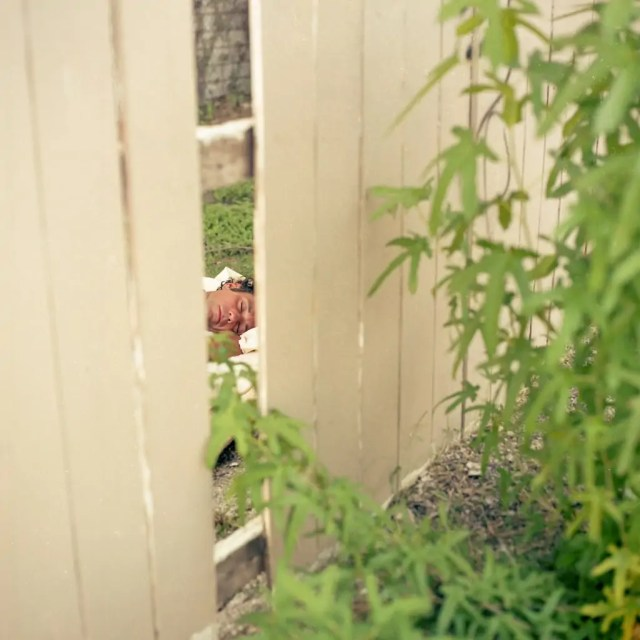 A man sleeping seen through a fence with a missing board in Dallas, Texas