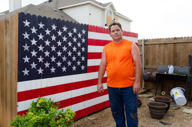 Man in front of his American flag painted fence
