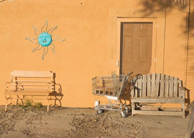 A bench, shopping cart, and blue sun in Adrian, Texas