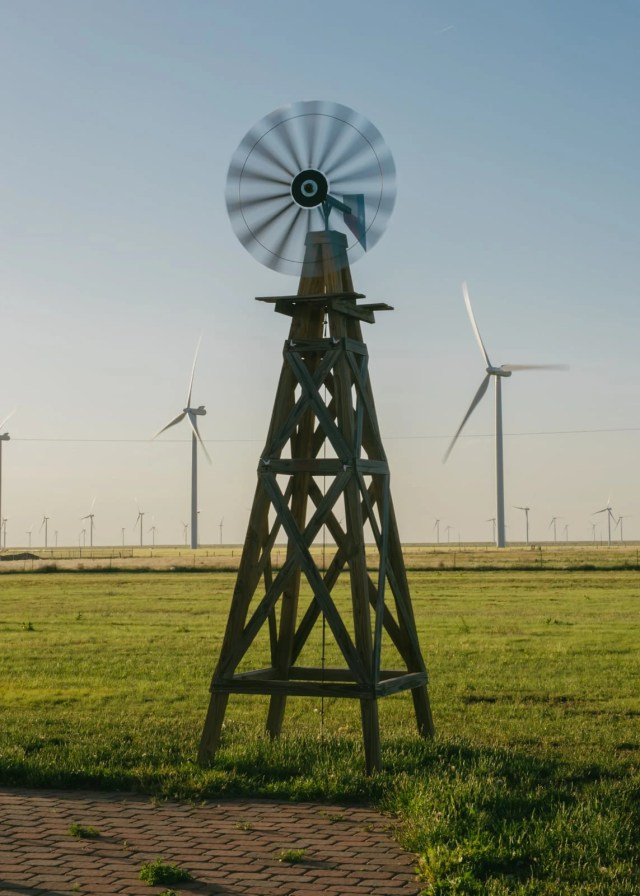 An old windmill by a wind farm