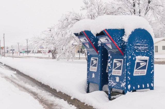 Blue mailboxes covered with snow