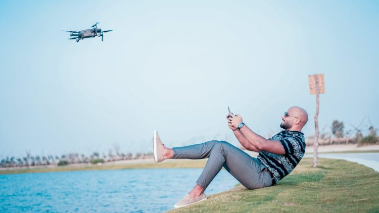 man controlling quadcopter drone