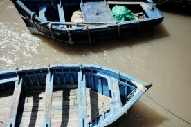 two blue boats in muddy water
