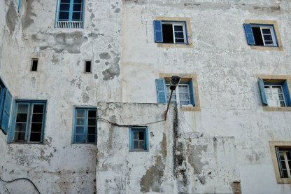 an old white wall with blue shutters