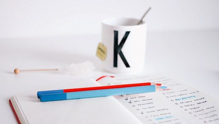 A coffee cup and to-do list on a table