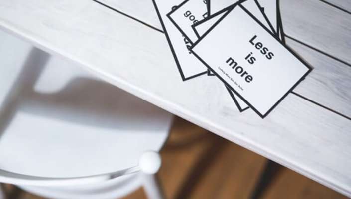 """Cards on a table that read """"Less is more"""""""