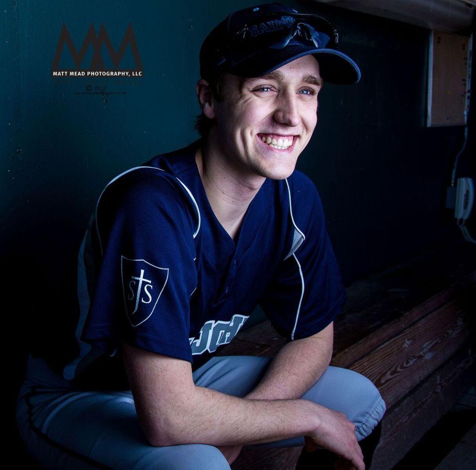 Teen smiling in baseball uniform during Erie PA senior portrait session
