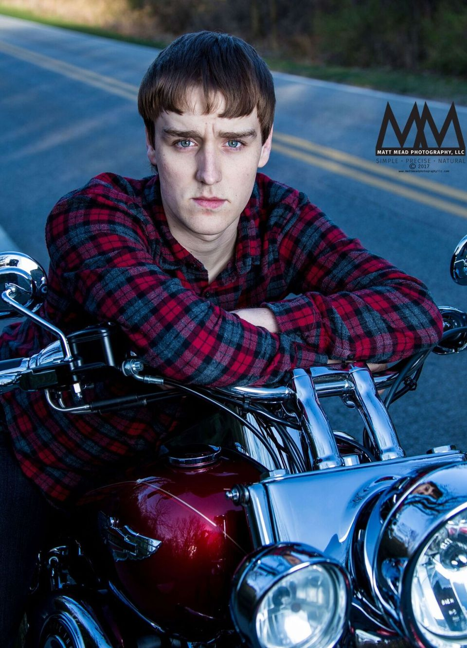 teen rests on motorcycle handlbars for Erie PA senior portrait session at Presque Isle state Park