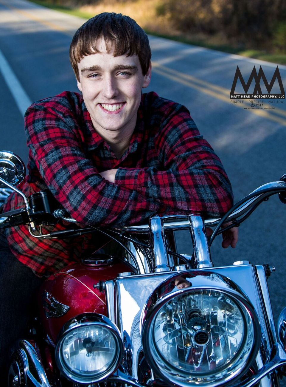 teen smiles while he rests on motorcycle handles for Erie PA senior portrait session at Presque Isle state Park