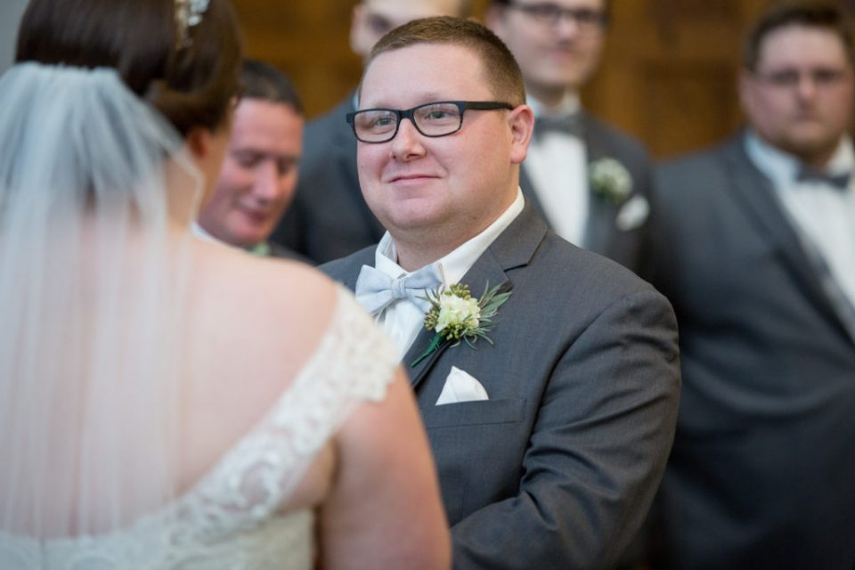 groom smiling during vows at winter wedding in Erie, PA
