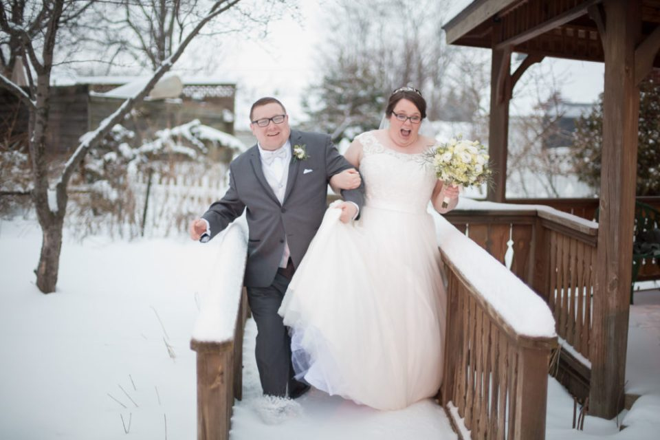 bride and groom sliding through the snow at winter wedding in Erie, PA