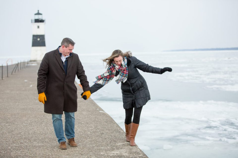 woman walks along North Pier's edge while holding fiance's hand in Erie, PA