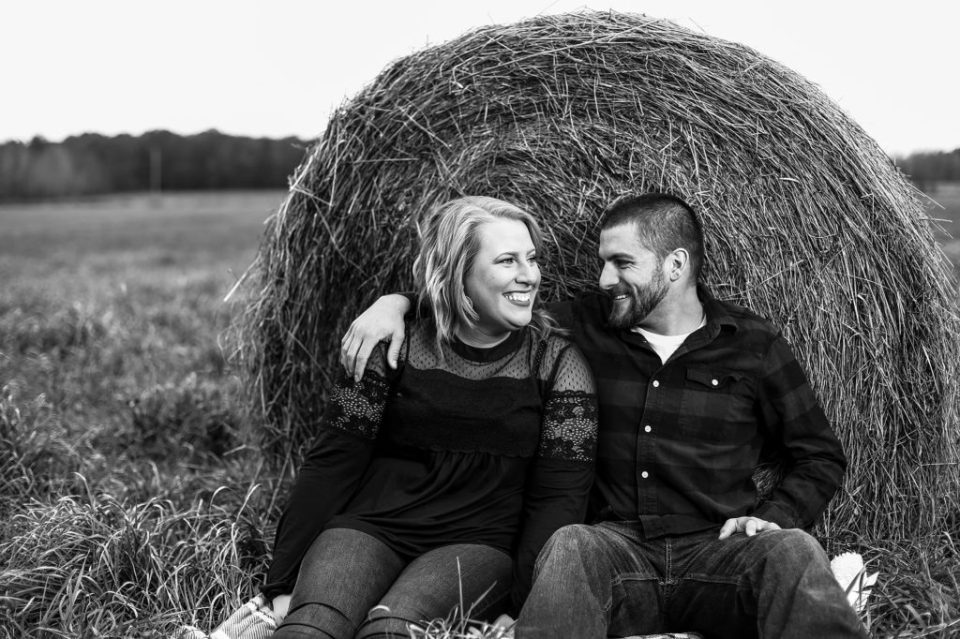 engaged couple smiling while sitting in front of a hay bale