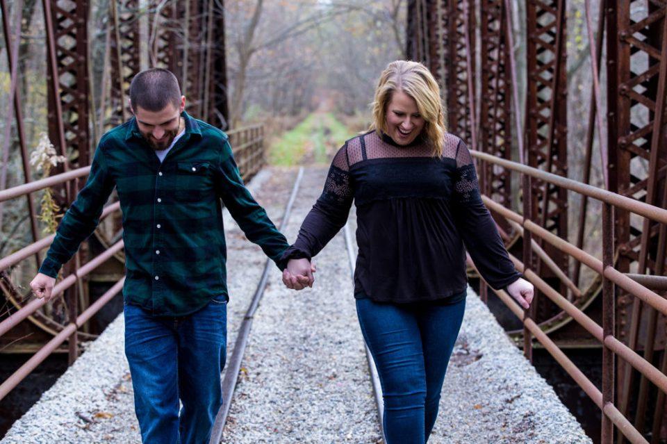 Erie, PA engaged couple walking across railroad bridge