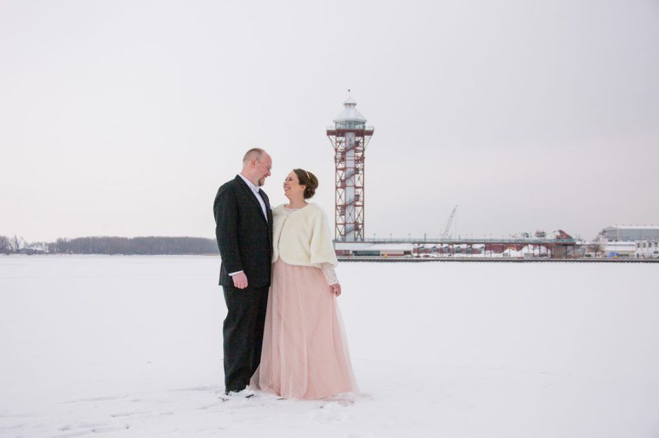 Erie, PA bride and groom look at each other and smile in front of the Bicentennial Tower in Erie, PA