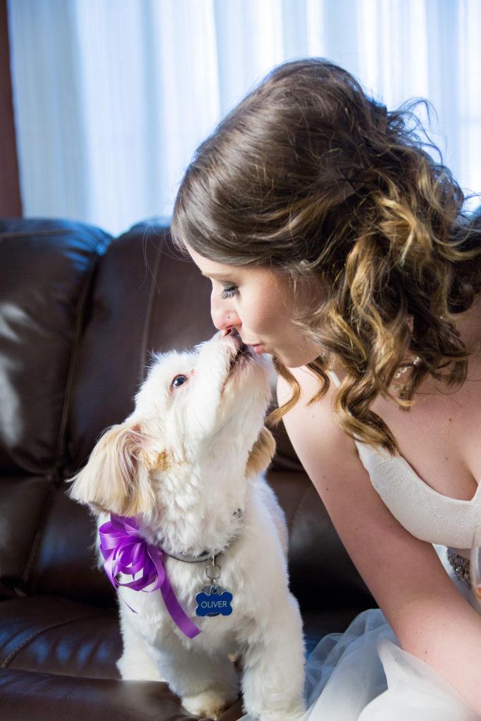 bride kissing her dog during wedding portrait session