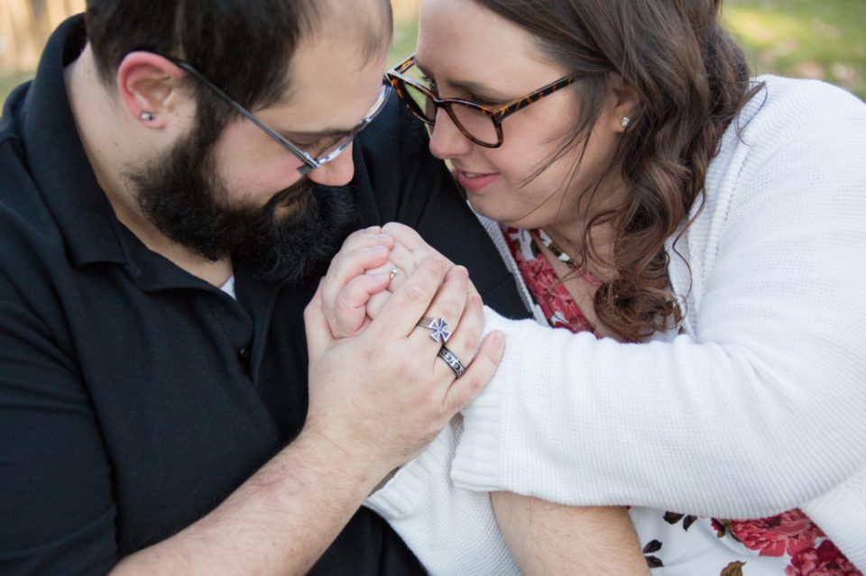 engaged couple holds hands and look at each other lovingly at Robin Hill Park engagement session