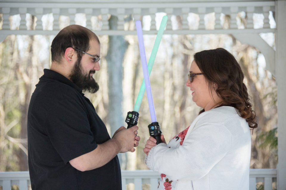 engaged couple pose at the ready for a lightsaber battle during their Robin Hill engagement session