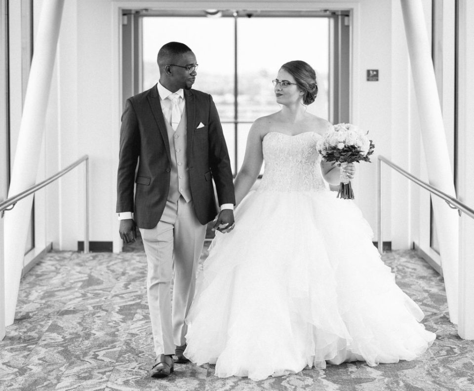 bride and groom walk the skybridge during first look photos at Sheraton Bayfront Hotel Erie, PA