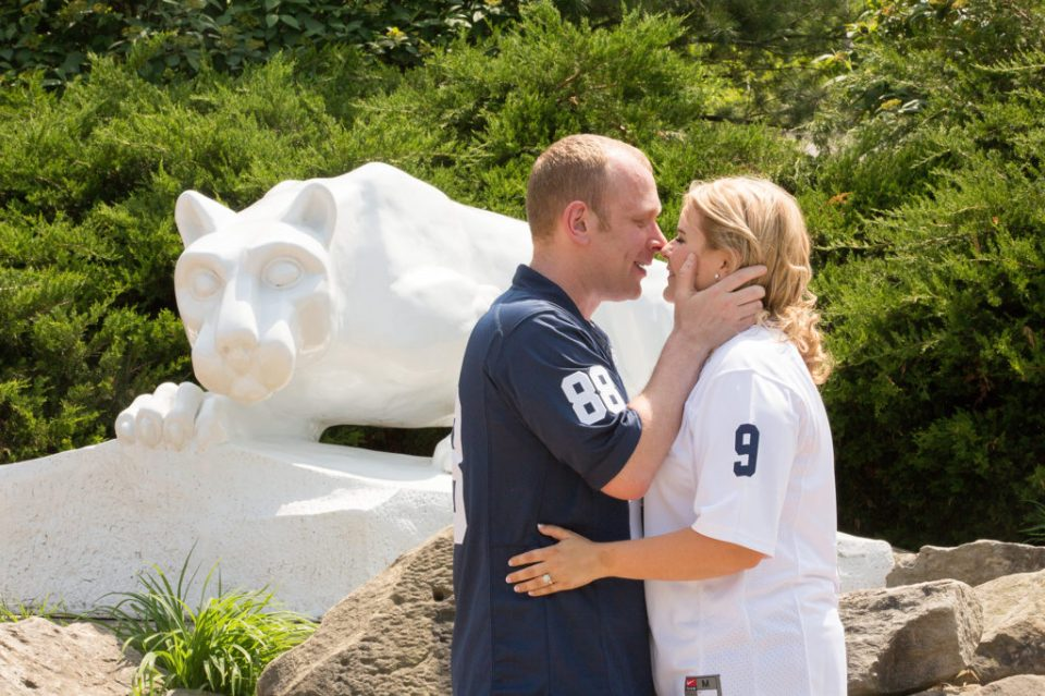 Engaged couple, wearing Penn State football jerseys,about to kiss in front of Nittany Lion statue at Penn State Behrend in Erie, PA