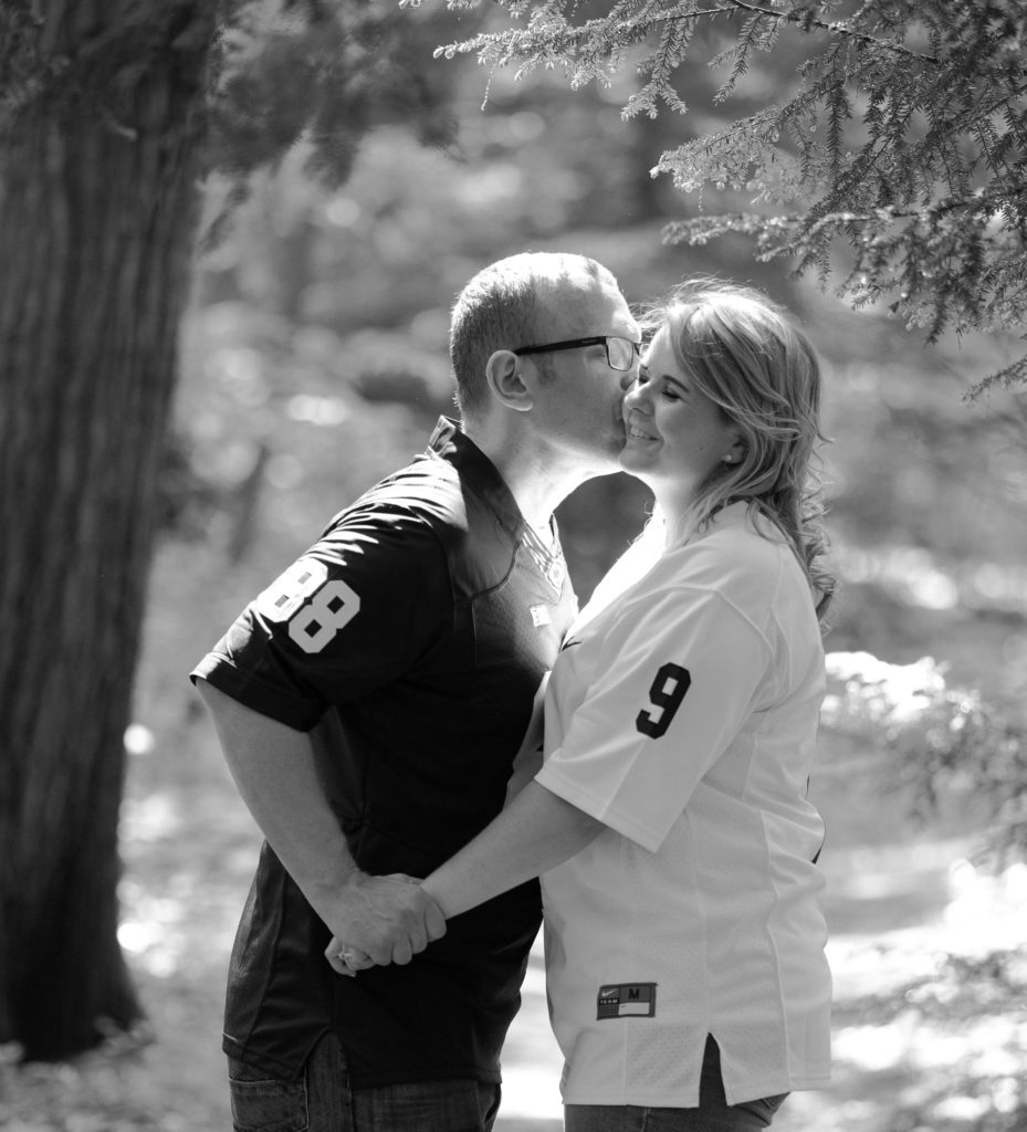black and white portrait of engaged couple kissing in the Arboretum on the campus of Penn State Erie