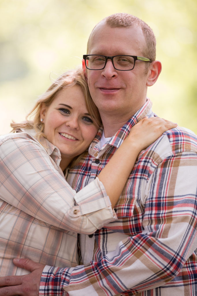 Engaged couple snuggles together in Penn State Erie engagement session