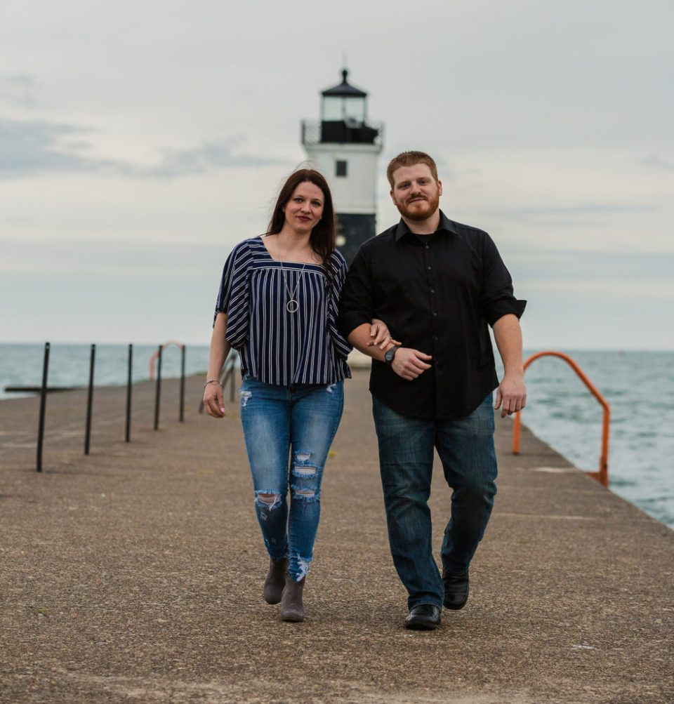 engaged couple walks along North Pier in Erie, PA