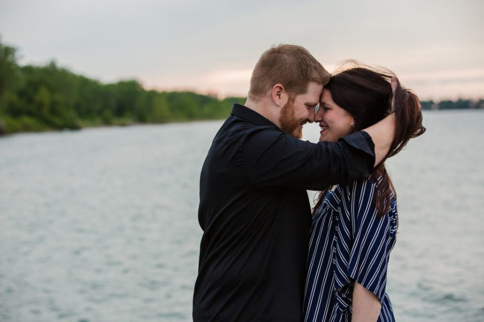 Man with hands in his fiancee's hair during engagement photos on North Pier in Erie PA