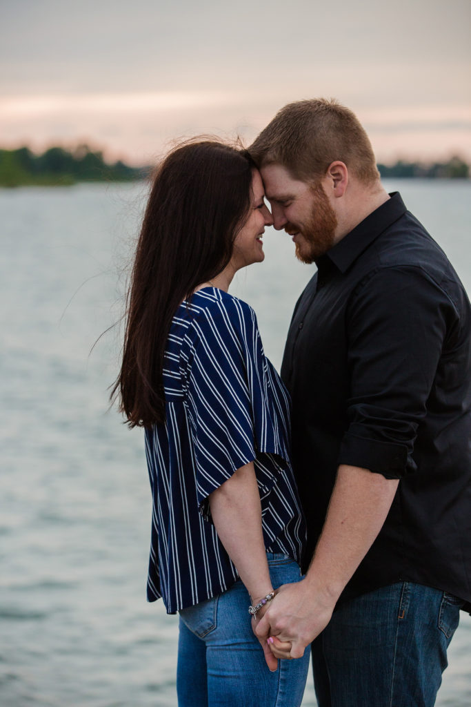 Engaged couple hold hands and touch foreheads for engagement photos on the North Pier in Erie PA