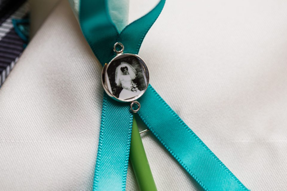 close up photo of teal ribbon with mom photo pinned on groom's lapel in Erie PA