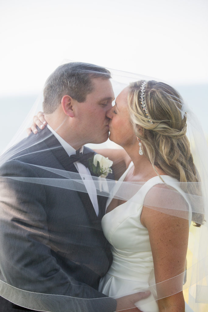 Erie PA bride and groom kiss under her veil during wedding portraits at Lawrence Park Golf Club