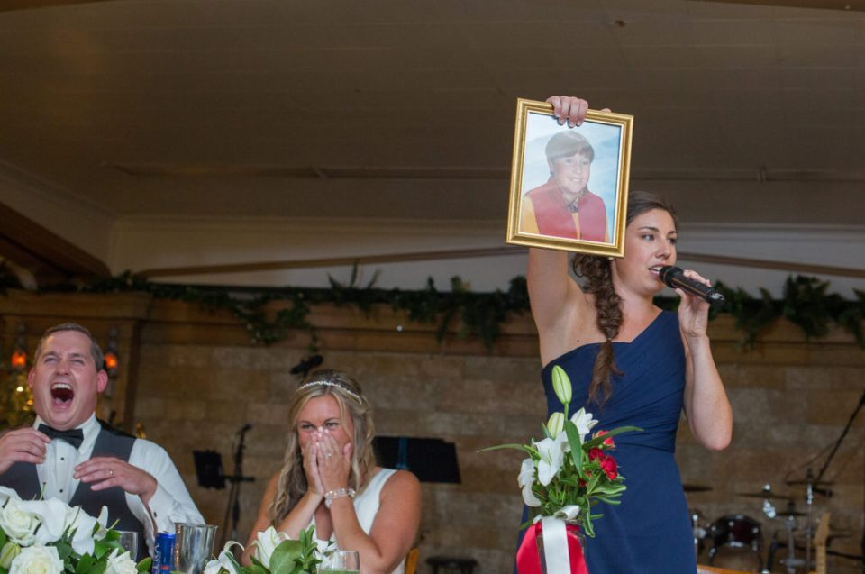 maid of honor and sister of the bride displays embarassing childhood picture during Erie PA wedding reception at Masonic Temple