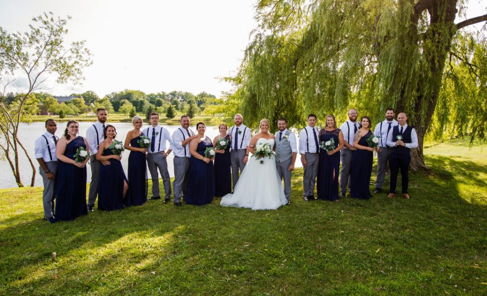 bridal party poses together under willow tree next to pond on campus at Edinboro University wedding