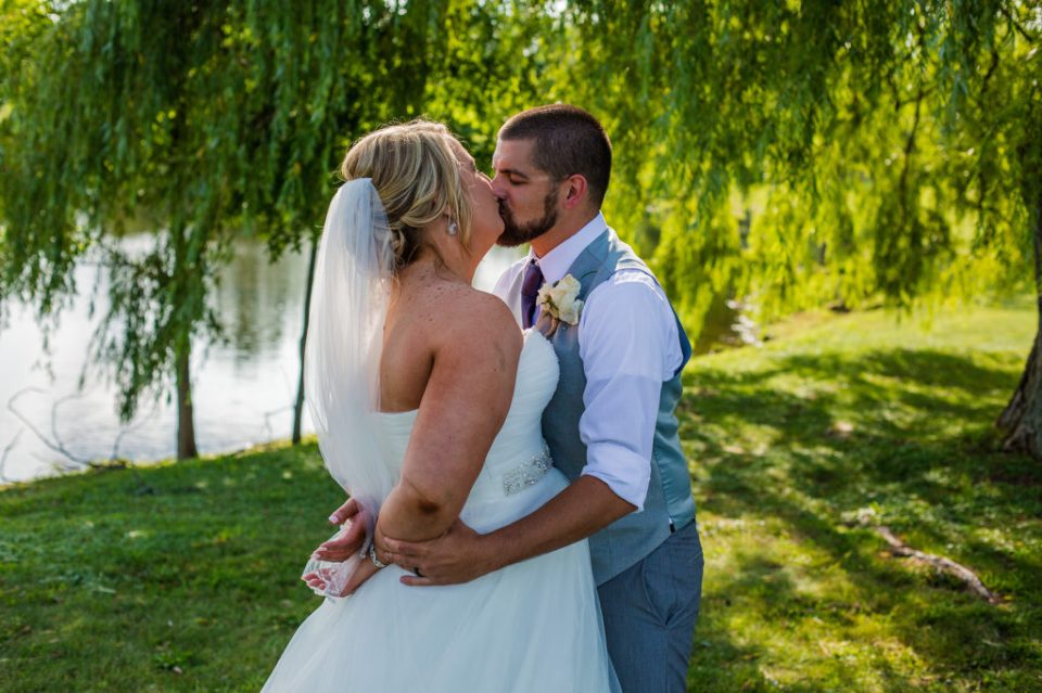 bride and groom kiss under willow trees at Edinboro University wedding