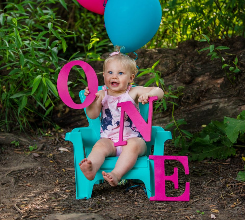 girl posing with letters for her first year photos at Frontier Park in Erie PA