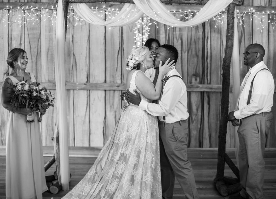bride and groom share first kiss at the end of their Betsy's Barn wedding ceremony