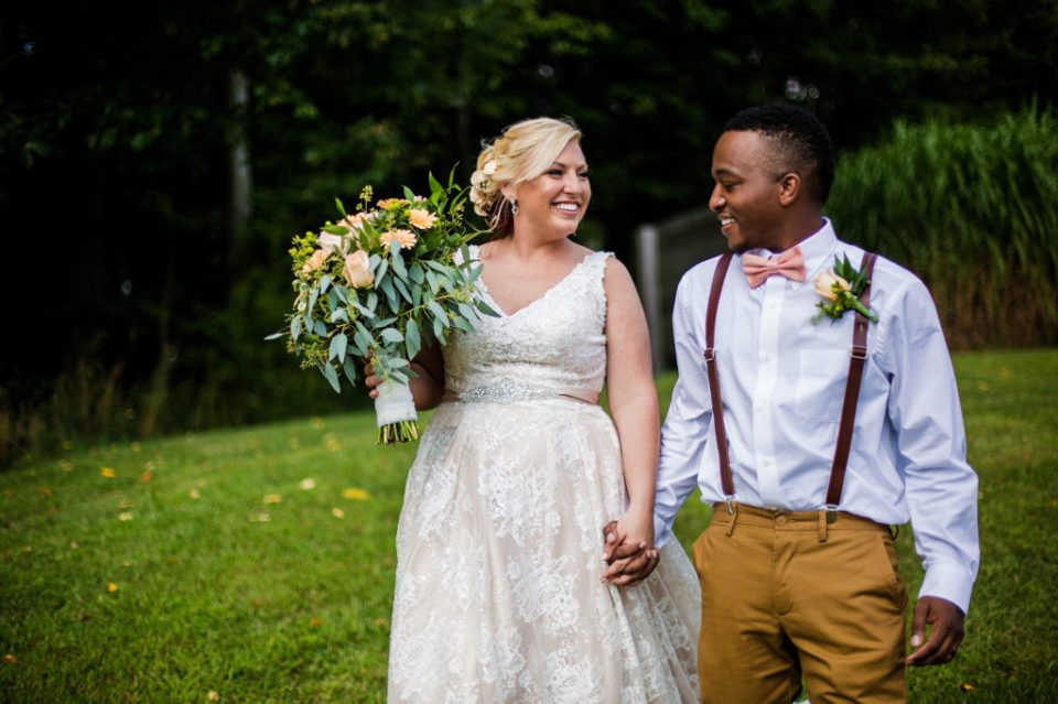 couple walks hand in hand at Betsy's Barn wedding