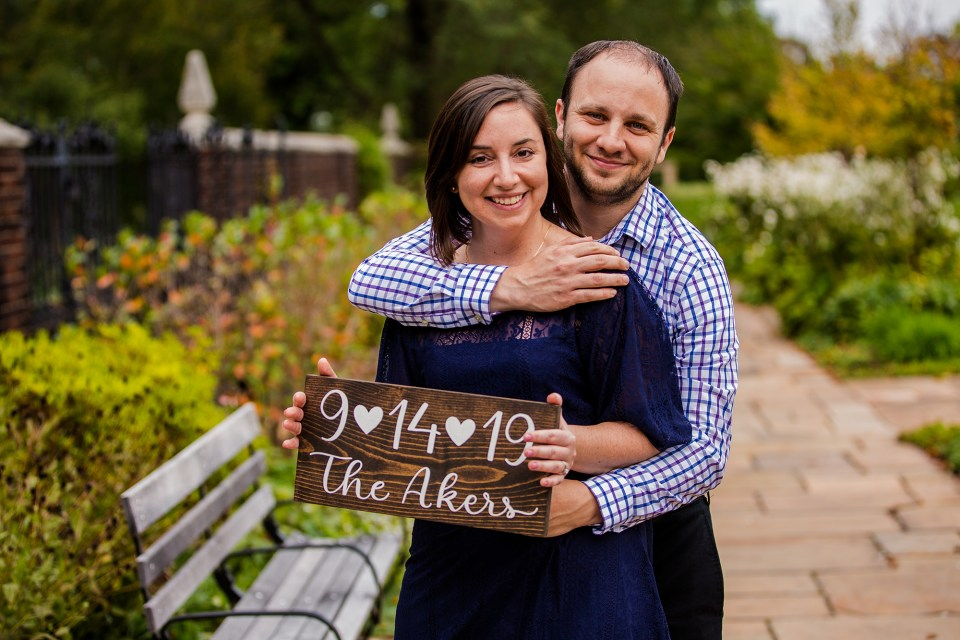 Pittsburgh PA engaged couple poses with a handmade sign announcing their wedding date in Mellon Park