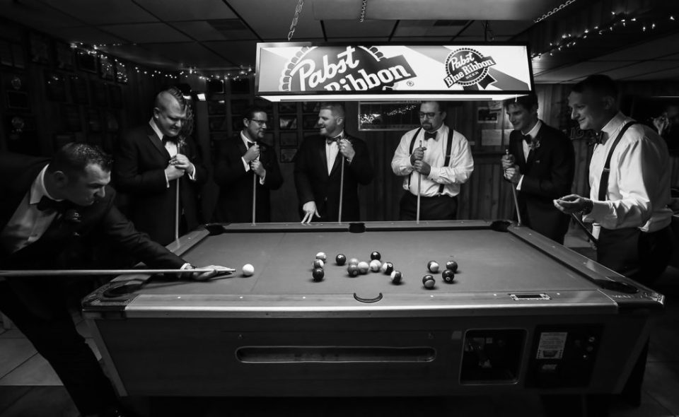 Iconic Black and White Bridal Portrait of the groomsmen reenacting the iconic portrait of the rat pack playing pool at Justin and Amandas Warner Theater Wedding